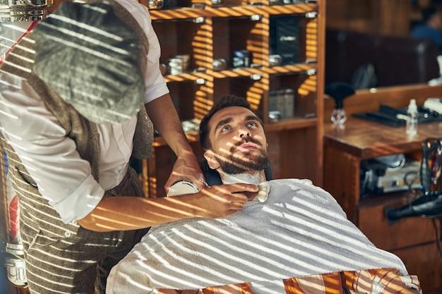Client de salon de coiffure se penchant en arrière dans un fauteuil avant la procédure de rasage