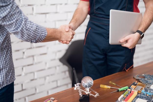 Le client serre la main avec le réparateur informatique.