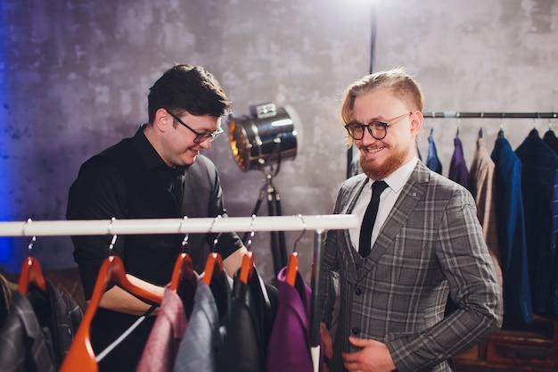 Client de sexe masculin au centre commercial essayant des vêtements d'affaires avec un assistant de magasin