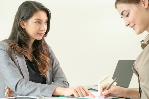 Un client signe un document pour acheter une maison et de l'immobilier