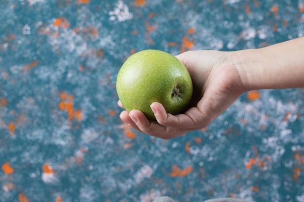 Client tenant une pomme à portée de main.