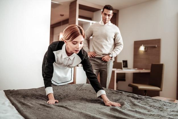 Client vulgaire. client vulgaire debout et regardant la jeune femme de chambre travailler tout en prévoyant de la harceler
