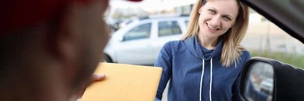 Une cliente appose sa signature sur les documents lors de la réception du colis du service de messagerie