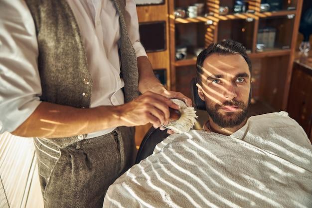 Une cliente brune d'un salon de coiffure en attente d'être rasée par un barbier