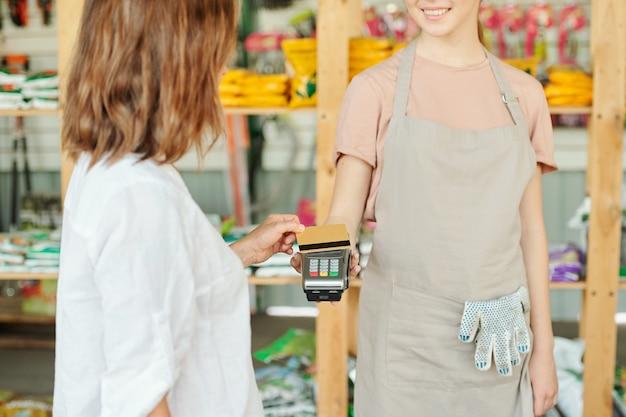 Une cliente brune tenant une carte de crédit sur un terminal de paiement détenu par une jeune vendeuse souriante d'un grand supermarché de jardinage