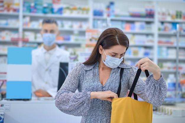 Cliente caucasienne d'âge moyen aux cheveux noirs et sérieuse dans un masque protecteur regardant dans son sac fourre-tout