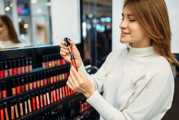Cliente contre vitrine dans la boutique de maquillage. choix de cosmétiques en magasin de beauté, maquillage