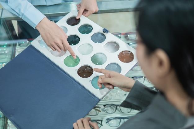 Une cliente avec un doigt pointant vers un échantillon de lentille lors du choix d'un type de lentille chez un opticien