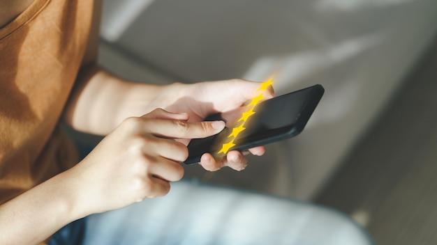 Une cliente donne une note de cinq étoiles sur un smartphone enquête de satisfaction sur l'expérience client