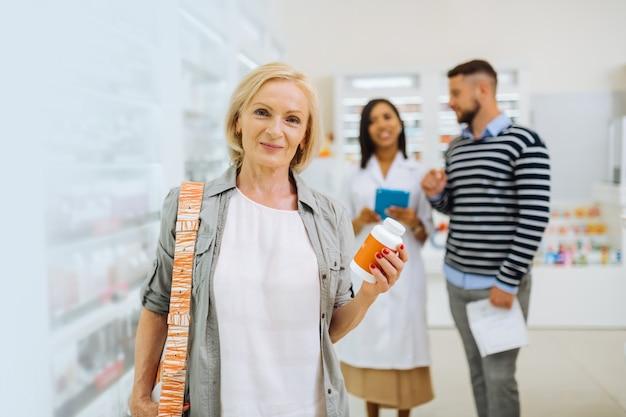 Cliente émotionnelle. gentille blonde gardant le sourire sur son visage tout en tenant un paquet avec des pilules