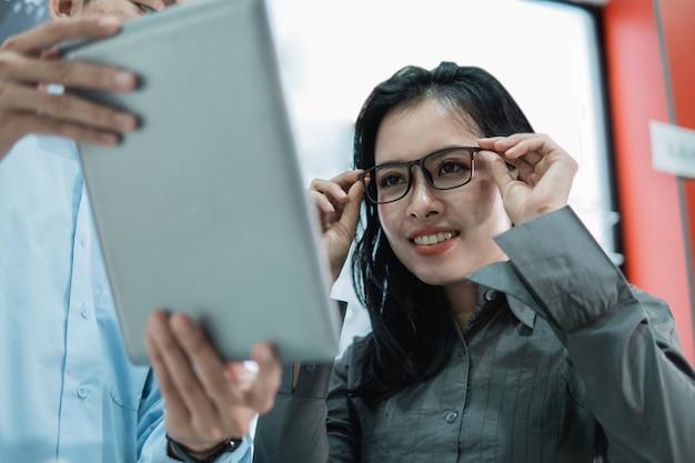 Une cliente essaie sur les lunettes de regarder l'écran de la tablette alors qu'elle est chez un opticien