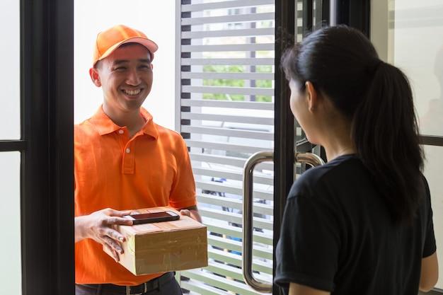 Cliente féminine ouvre la porte pour recevoir le colis du livreur