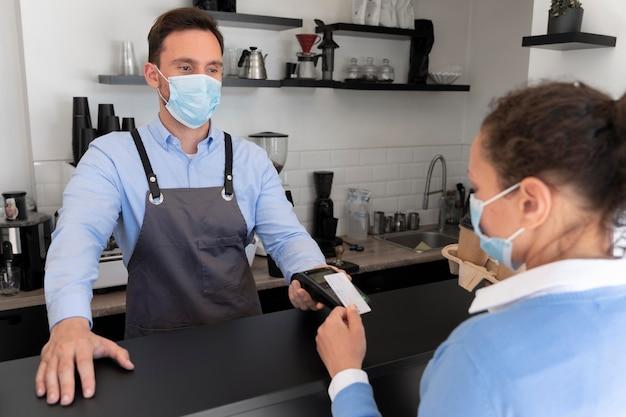 Cliente féminine payant des plats à emporter avec carte de crédit