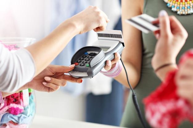 Cliente féminine payant des vêtements en boutique