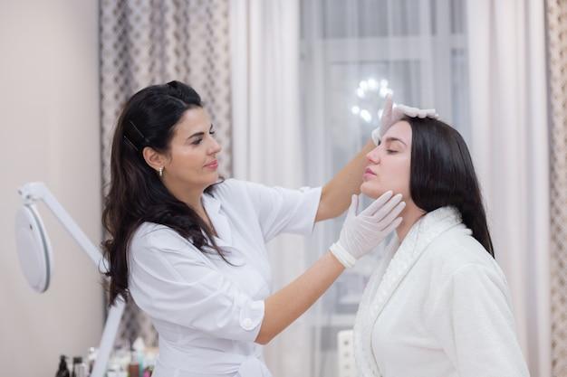Une cliente lors d'un rendez-vous esthéticienne, consultation, mise en forme du visage, préparation aux procédures à venir, examen visuel des zones à problèmes
