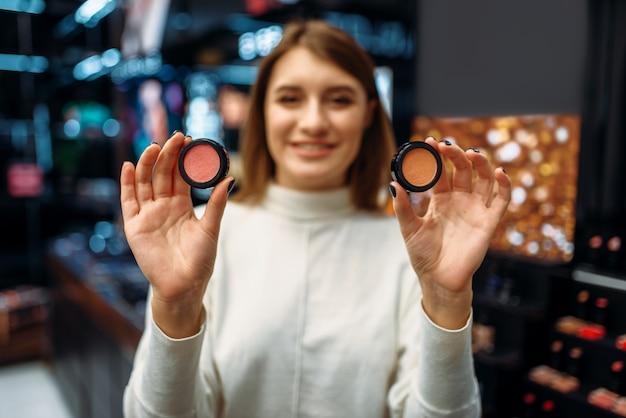 Une cliente montre des cosmétiques dans la boutique de maquillage.