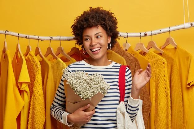 Une cliente optimiste passe du temps libre à faire du shopping en magasin, pose avec bouquet et sac contre des vêtements jaunes sur des étagères, concentrée de côté avec un large sourire