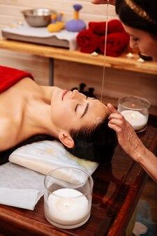 Cliente paisible. belle femme attentionnée allongée entre des bougies parfumées sur une table pendant que le maître verse de l'huile sur elle