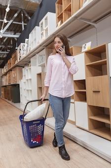 Cliente parlant sur son téléphone mobile, marchant avec panier au magasin de meubles
