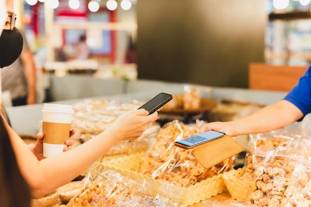 Une cliente portant un masque de protection fait une vendeuse de paiement mobile sans contact dans un magasin de détail.