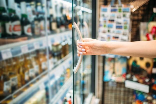 Une cliente prend une bière au supermarché. femme, magasinage alimentaire