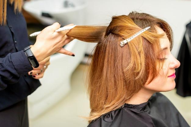 La cliente recevant une coupe de cheveux au salon de beauté, jeune femme profitant d'une nouvelle coiffure.