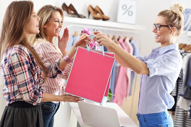 Cliente recevant des sacs à provisions en boutique