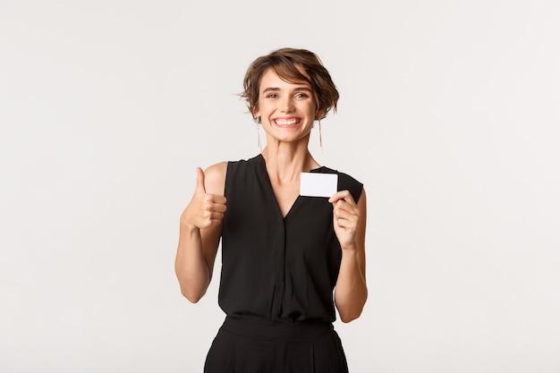 Cliente satisfaite montrant sa carte de crédit
