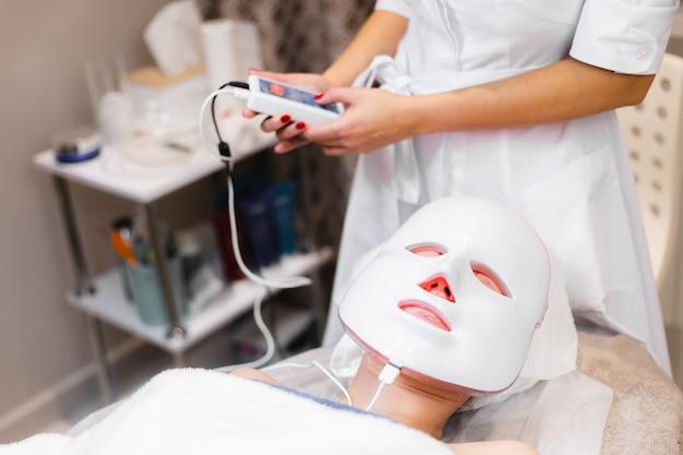 La cliente se trouve dans le salon sur la table de cosmétologie avec un masque blanc sur son visage