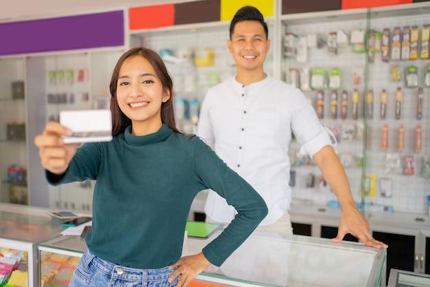 Une cliente sourit en montrant une carte de crédit pour un paiement sans numéraire à l'appareil photo