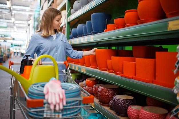 Clientèle féminine à l'étagère avec des pots, boutique de jardinage. femme d'acheter du matériel en magasin pour la floriculture, l'achat d'instruments de fleuriste
