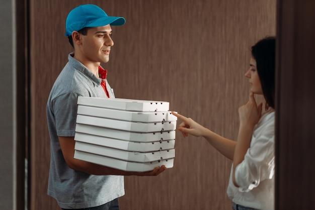 Clientèle féminine à la porte et livreur de pizza