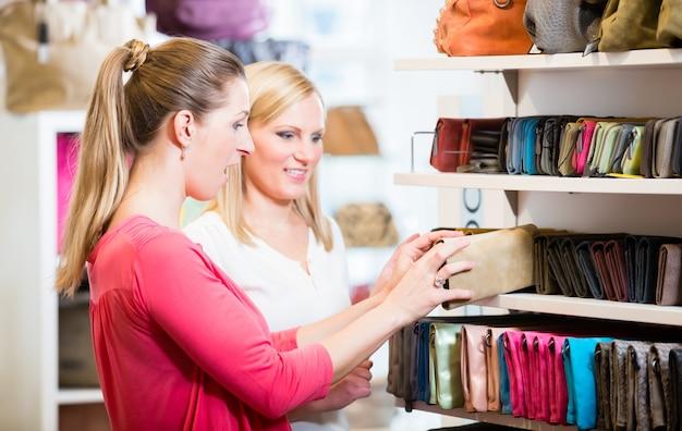 Les clientes en magasin shopping à la recherche de portefeuilles et sacs à main