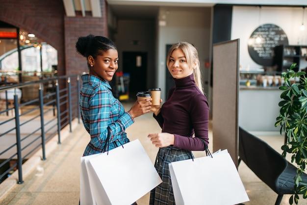 Clients féminins blancs et noirs avec des sacs à provisions dans le centre commercial. accro du shopping dans les magasins de vêtements, achats, mode