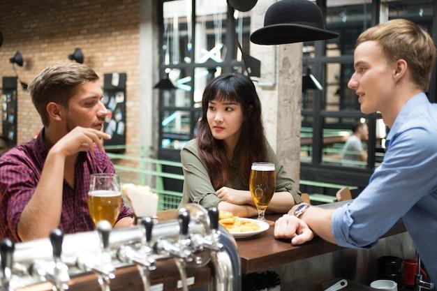 Les clients font la conversation avec bartender dans pub