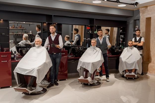 Clients masculins assis dans des chaises de coiffeur recouverts de coupe de cheveux.