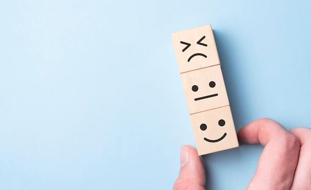 Les clients ont choisi à la main l'icône du visage souriant et le symbole cinq étoiles sur un cube en bois sur une table