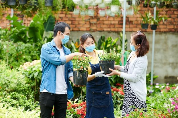 Clients parlant au travailleur du centre de jardinage