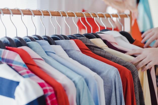 Les clients qui choisissent des chemises sur une corde à linge.