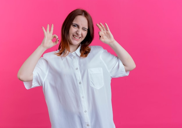 Clignoté jeune fille rousse montrant le geste okey isolé sur un mur rose avec espace de copie