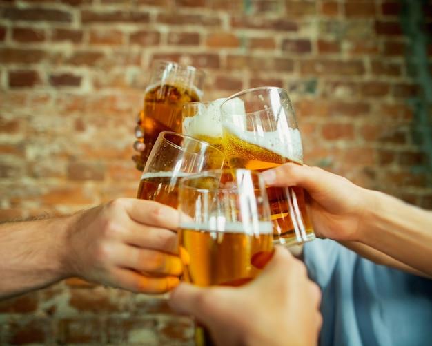 Clignotement en gros plan. jeune groupe d'amis buvant de la bière, s'amusant, riant et célébrant ensemble. femmes et hommes avec des verres à bière. oktoberfest, amitié, convivialité, concept de bonheur.