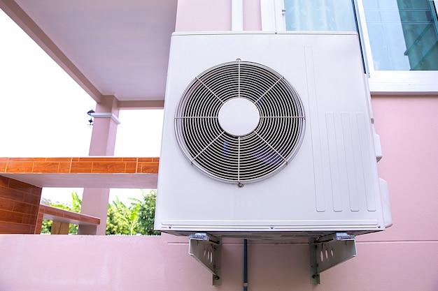 Le climatiseur est installé à l'extérieur du bâtiment.