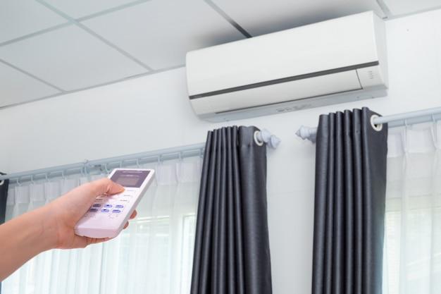 Climatiseur à télécommande en appuyant sur la main dans la chambre.