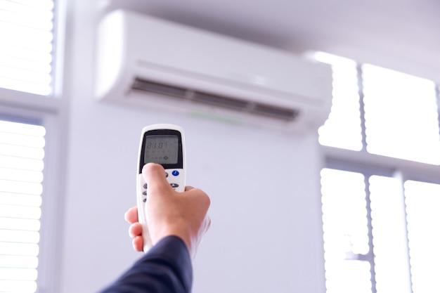 Climatiseur avec télécommande, à l'intérieur de la pièce avec manette de contrôle à distance.