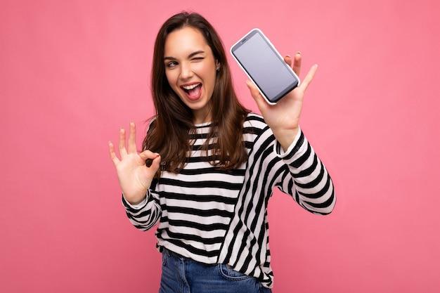 Clin d'œil belle jeune femme heureuse portant un pull rayé isolé sur fond avec espace de copie montrant un geste ok regardant la caméra montrant l'affichage de l'écran du téléphone portable