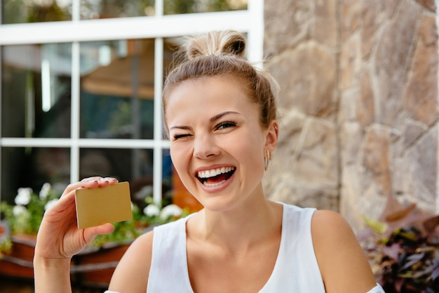 Un clin de œil femme tenant une carte de crédit