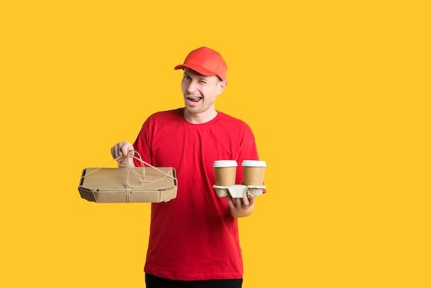 Un clin d'œil livreur de courrier dans un bonnet rouge et un t-shirt détient des boîtes et du café sur jaune