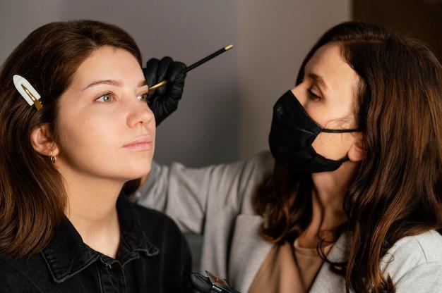 Clinicien féminin faisant un traitement des sourcils pour femme