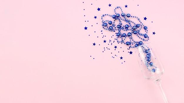 Clinquant bleu dans un verre sur fond d'espace copie rose