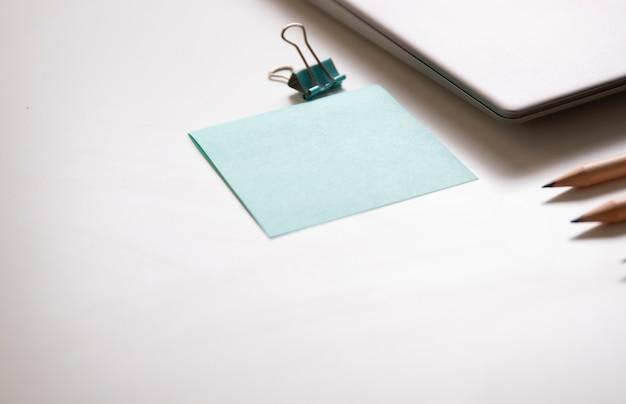 Clip de reliure et bloc-notes près du labtop sur la table blanche